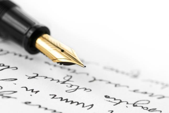 Caneta-tinteiro e papel com escrita.